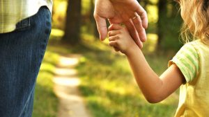 the parent holds the hand of a small child; Shutterstock ID 334181882; user id: 14504460; user email: tougao@ksjgs.com; user_country: China; discount: 5%